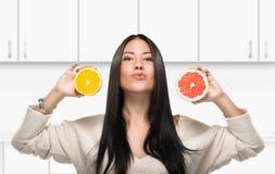 拿着一个柑橘的深色的女孩在厨房里 库存照片