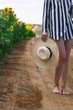 拿着一个柳条帽子的妇女在向日葵领域旁边 免版税图库摄影