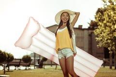 拿着一个桃红色可膨胀的气垫的美丽的迷惑的快乐的妇女 免版税库存图片