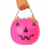 拿着一个桃红色塑料南瓜的孩子 免版税库存图片