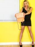 拿着一个桃红色提包的年轻女商人 库存图片