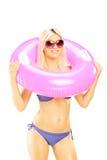 拿着一个桃红色游泳圆环的比基尼泳装的白肤金发的性感的女性 免版税库存图片