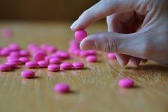 拿着一个桃红色药片的男性手作为药房的标志 免版税图库摄影