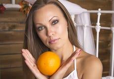 拿着一个桔子用两只手的年轻美丽的妇女 画象 免版税图库摄影