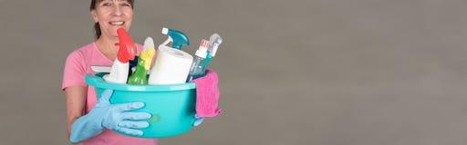 拿着一个桶用清洁设备的主妇 免版税库存图片