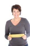拿着一个棕色信包的微笑的妇女 免版税库存照片