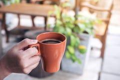 拿着一个棕色杯子热的咖啡的手早晨有迷离背景 免版税库存照片