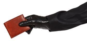 拿着一个棕色皮革钱包的黑衣服的窃贼 库存图片