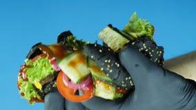 拿着一个水多的汉堡用一个黑小圆面包的一只黑手套的手的特写镜头洒与芝麻和牛肉小馅饼和断裂 股票录像