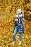 拿着一个热水瓶用茶的一条白色帽子和容量围巾的逗人喜爱的少年女孩在秋天公园 免版税库存照片