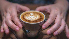 拿着一个热的咖啡杯的手 库存图片