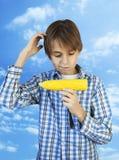 拿着一个煮沸的玉米的男孩 免版税库存图片
