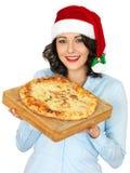拿着一个煮熟的薄饼的圣诞老人帽子的少妇 库存照片