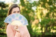 拿着一个爱好者的美丽的少妇在公园 库存照片
