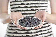 拿着一个牌照用蓝莓的少妇 图库摄影