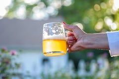 拿着一个玻璃杯子啤酒的妇女在夏天 免版税库存图片