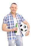 拿着一个瓶啤酒和橄榄球的年轻人 免版税库存图片
