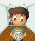 拿着一个瓶子在书架前面的糖果的男孩 免版税库存照片