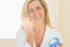拿着一个瓶子面霜的喜悦的妇女在手和申请上 免版税库存照片