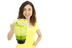 拿着一个瓶子绿色蔬菜汁的健康吃的妇女 免版税图库摄影