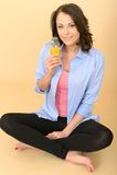拿着一个瓶橙汁的可爱的健康愉快的少妇 免版税图库摄影