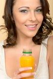 拿着一个瓶橙汁的可爱的美丽的少妇 库存照片