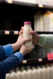 拿着一个瓶牛奶的孩子 免版税库存图片