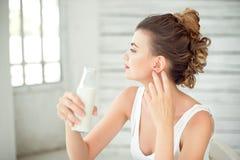 拿着一个瓶牛奶的美丽的妇女在她的手上 深色的有布朗颜色易洛魁族人头发的女孩佩带的白色汗衫 免版税图库摄影