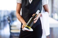 拿着一个瓶白葡萄酒和毛巾的女服务员的中间部分 免版税库存图片