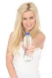 拿着一个瓶矿泉水的适合的健康愉快的可爱的年轻白肤金发的妇女 库存图片