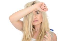 拿着一个瓶矿泉水的适合的健康疲乏的年轻白肤金发的妇女 免版税库存照片