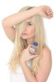 拿着一个瓶矿泉水的适合的健康年轻自然白肤金发的妇女 免版税库存图片