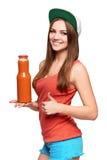 拿着一个瓶红萝卜汁的愉快的青少年的女孩 库存图片