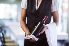 拿着一个瓶红葡萄酒和毛巾的女服务员的中间部分 库存图片