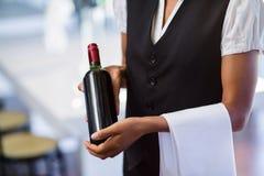 拿着一个瓶红葡萄酒和毛巾的女服务员的中间部分 免版税库存照片