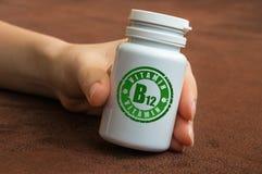 拿着一个瓶药片的人的手用维生素B12 免版税库存图片