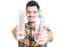 拿着一个瓶水和温度计的微笑的男性 库存图片