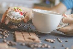 拿着一个甜蛋糕和一杯咖啡在黑暗的桌上的接近的手早晨f 免版税库存照片