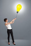 拿着一个电灯泡气球的俏丽的夫人 图库摄影