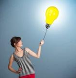 拿着一个电灯泡气球的俏丽的夫人 免版税图库摄影