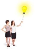 拿着一个电灯泡气球的愉快的妇女 免版税库存照片