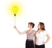 拿着一个电灯泡气球的愉快的妇女 库存图片