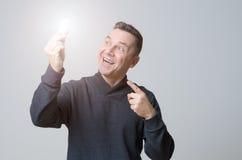 拿着一个电灯泡的有动机的中年人 免版税库存照片