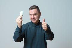拿着一个电灯泡的有动机的中年人 免版税库存图片