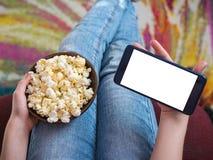 拿着一个电话有剪报背景的女孩 一碗在儿童` s膝部的玉米花 免版税库存图片