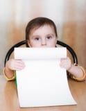 拿着一个白纸的婴孩。 免版税图库摄影