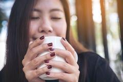 拿着一个白色杯子与感到的热的咖啡的一名美丽的亚裔妇女的特写镜头图象愉快 免版税库存图片