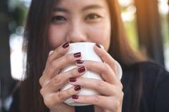 拿着一个白色杯子与感到的热的咖啡的一名美丽的亚裔妇女的特写镜头图象愉快 免版税库存照片