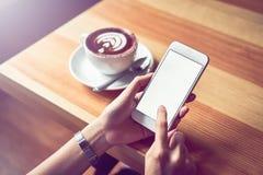 拿着一个白色电话的女孩有黑屏在咖啡馆和咖啡在桌上 免版税库存图片