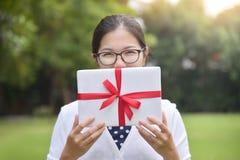 拿着一个白色礼物盒的亚裔女性 免版税库存图片